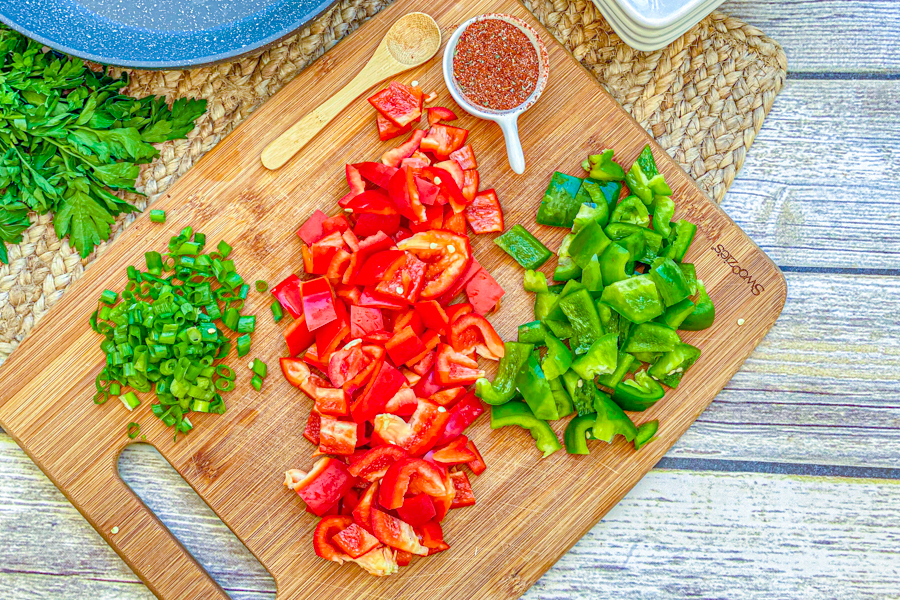 Cutting board with diced bell peppers and diced green onions on top.