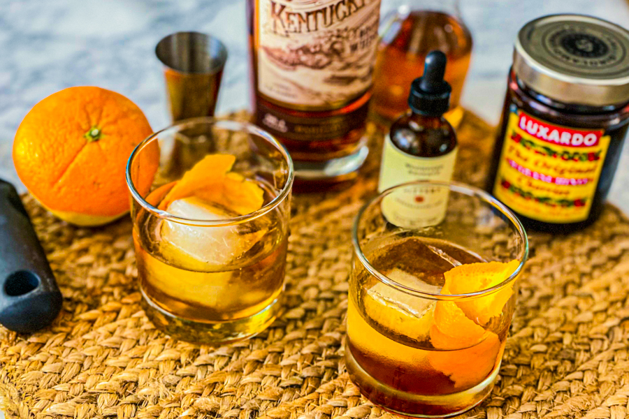 Our Kentucky Owl Old Fashioned on a placemat with all the ingredients around it.
