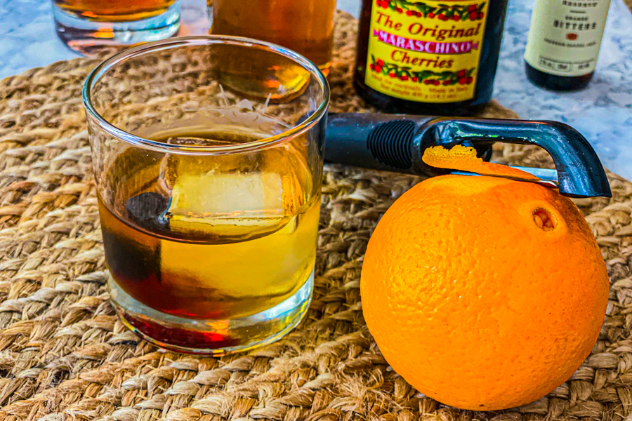 A glass of bourbon next to a orange being peeled by a vegetable peeler.