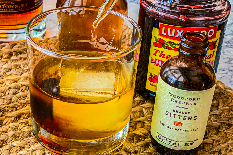 A glass of bourbon with a dropper og bitters going into it.