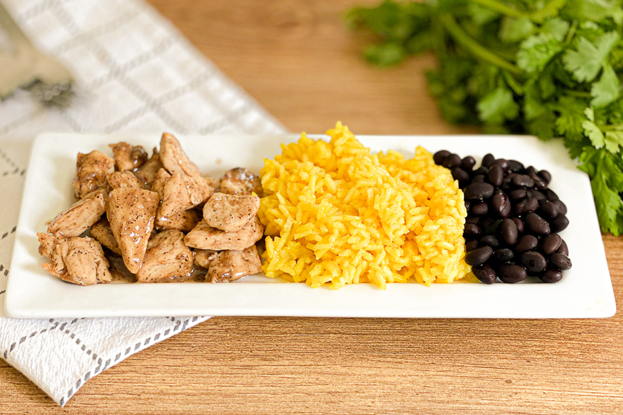 Fiesta Lime Chicken on a plate with yellow rice and black beans
