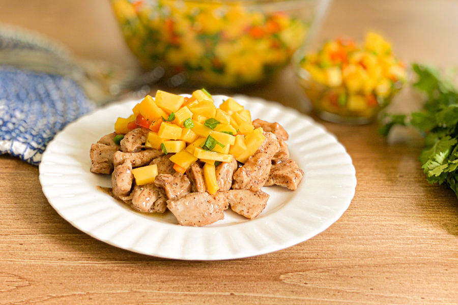 Fiesta Lime Chicken on a plate with Easy Mango Salsa on top