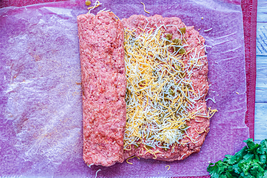 Ground beef mixture covered in green chiles and shredded cheese being rolled into a loaf.