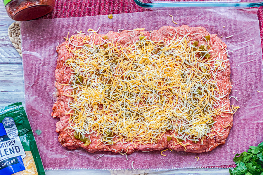Ground beef mixture covered in green chiles and shredded cheese.