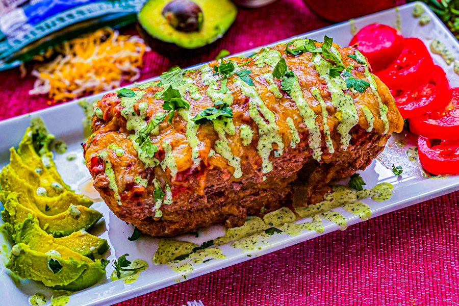 The final of our Mexican Meatloaf on a serving dish garnished with ranch, cilantro, avocados and diced tomatoes.