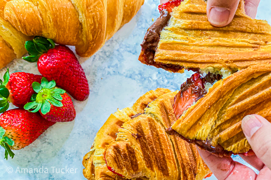 Tearing a Nutella and Strawberry Croissant in half with strawberries popping out.