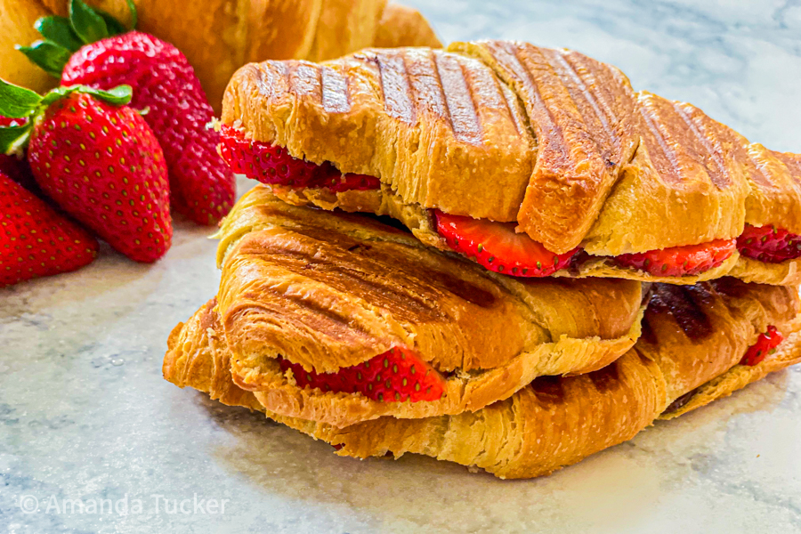Nutella and Strawberry Croissants stacked on top of each other next to fresh strawberries.