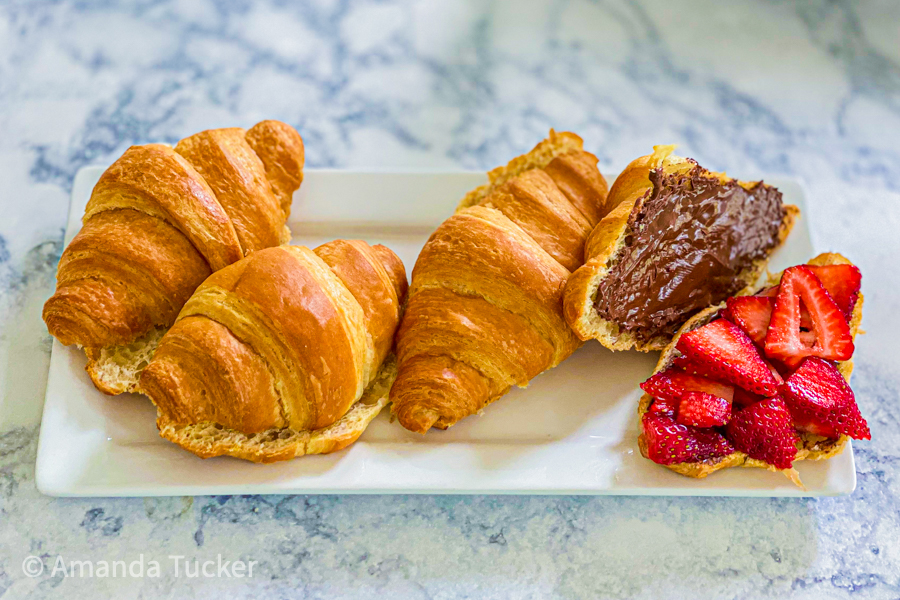 Croissants on a plate with nutella spread on 1 with strawberries.