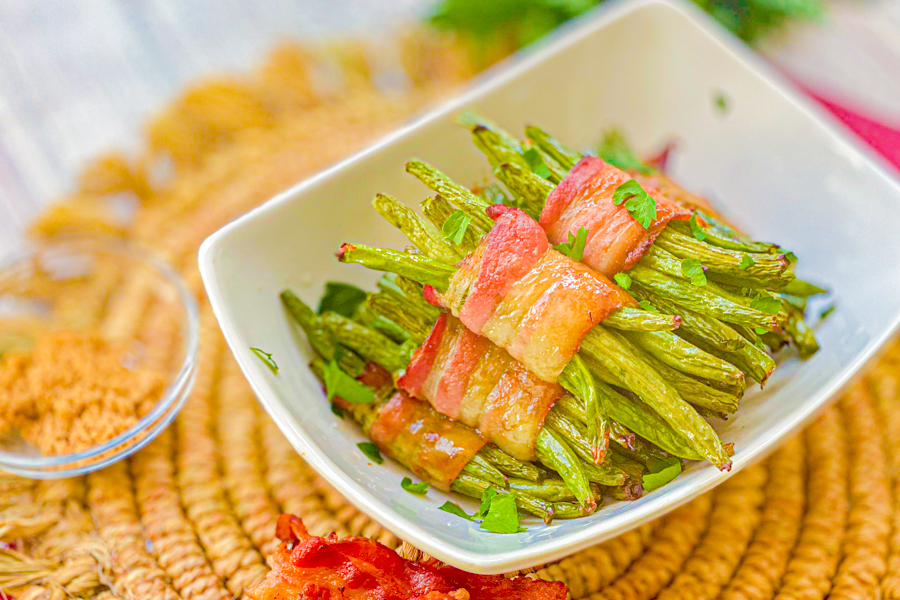 Our Sweet Bacon Wrapped Green Beans on a white serving dish on a placemat.