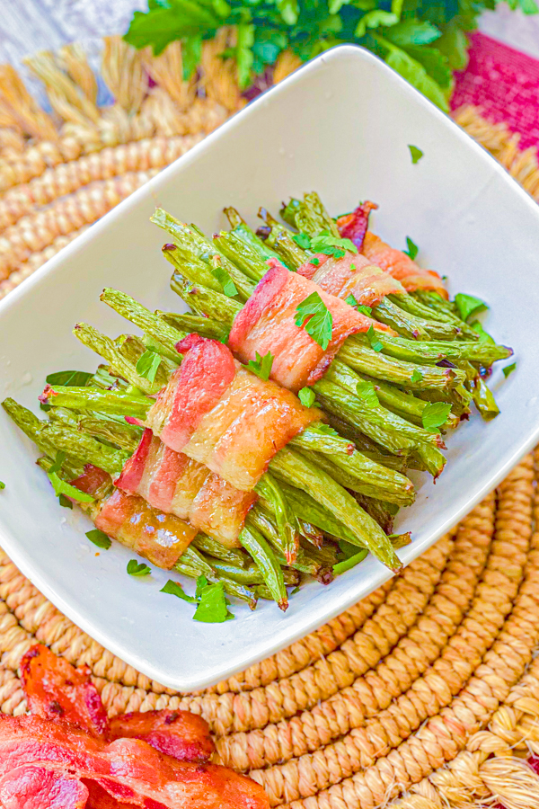 Our Sweet Bacon Wrapped Green Beans in a white dish on a table after being cooked