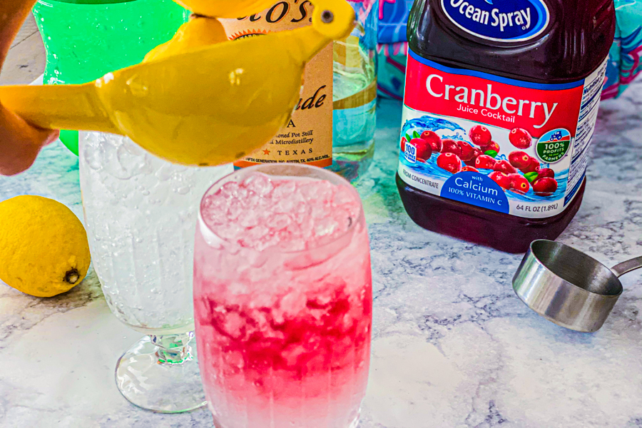 Fresh squeezed lemon juice being poured over a cup full of sprite and cranberry juice.