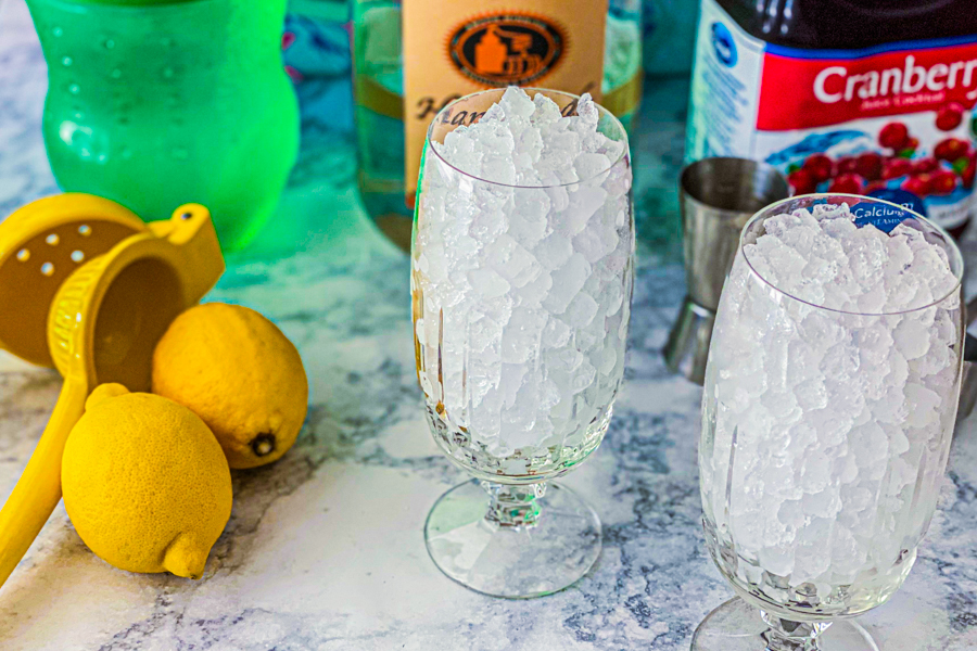 Two glasses filled with ice being surrounded by the ingredients for our Summertime Cocktail