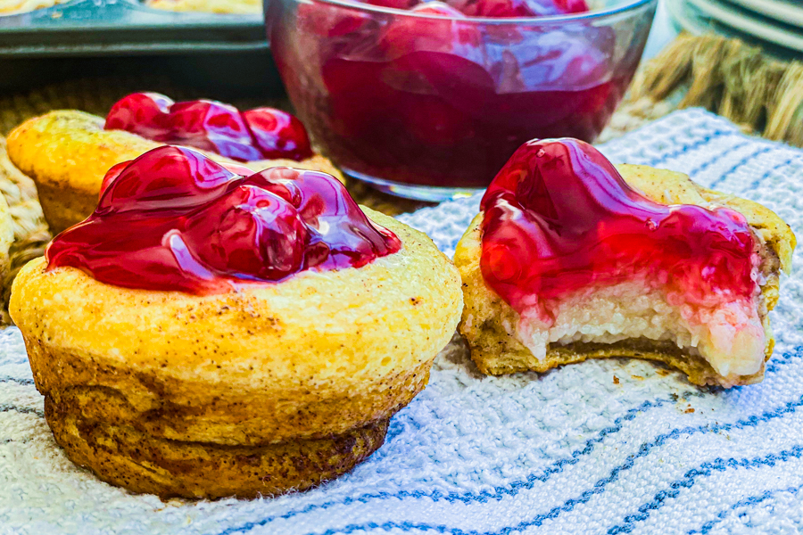 The 5 Ingredient Cherry Tarts with a bite missing on a while napkin next to a clear bowl of cherry filling.