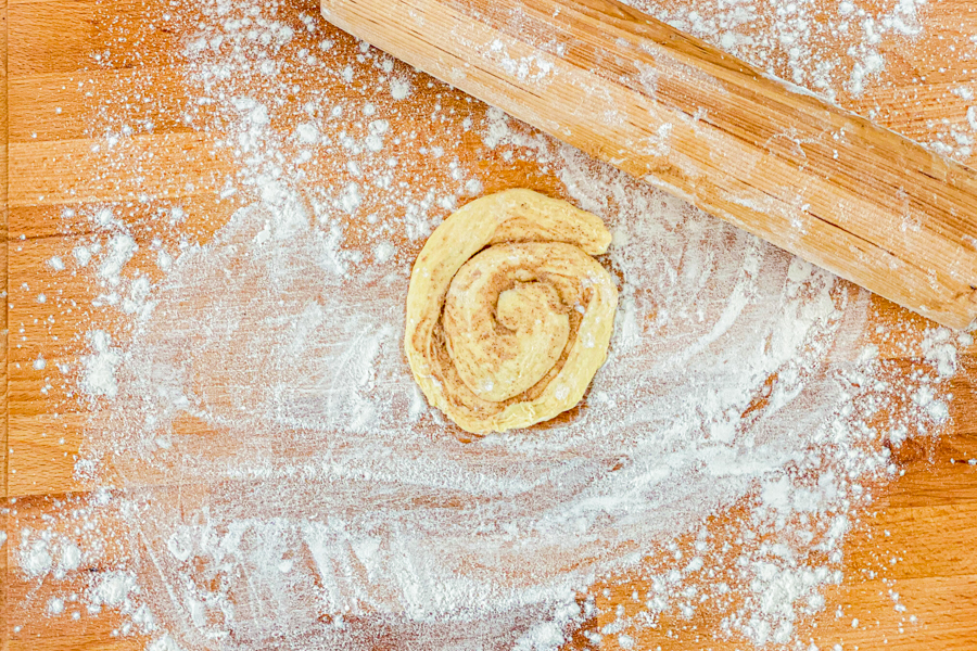 A raw cinnamon roll on a flour dusted cutting board next to a rolling pin.