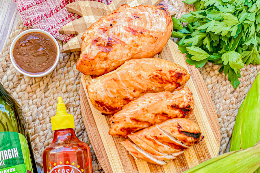 A final shop of our Brown Sugar Sriracha Chicken Marinade on chicken on a wooden cutting board.