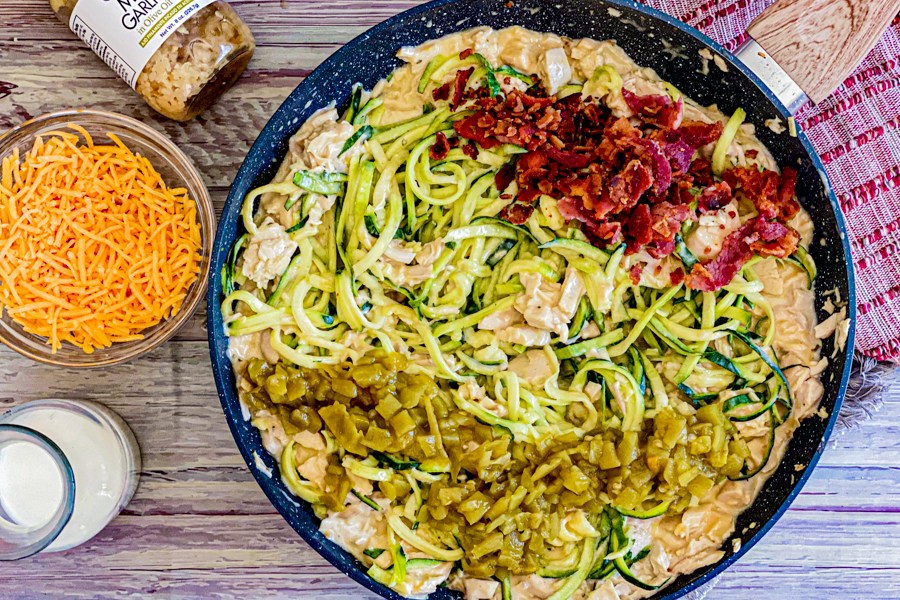 A skillet with a mixture of ranch, milk, garlic and chicken and zoodles with bacon and green chiles added on top.