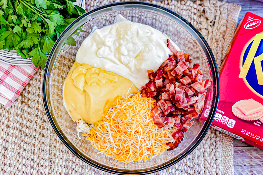 A glass mixing bowl on top of a table with yogurt, cheese, bacon, chicken, ranch seasoning, and cream of soup before mixing.
