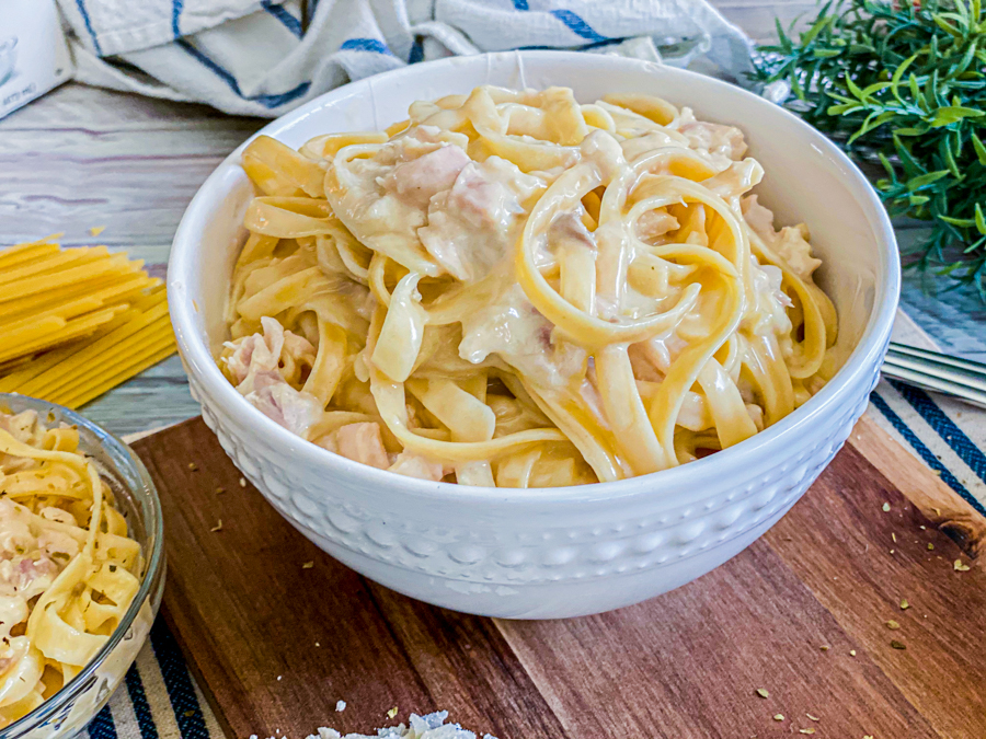 The Quick Instant Pot Chicken Alfredo all done cooking, in a white bowl, ready to be served.