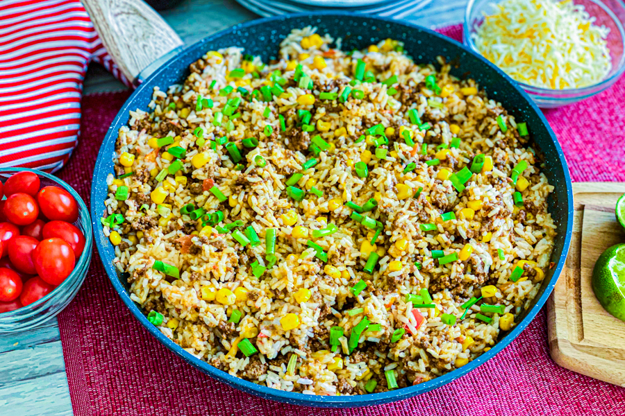 The Quick Taco Rice Bowl garnished with green onions on a red placemat.