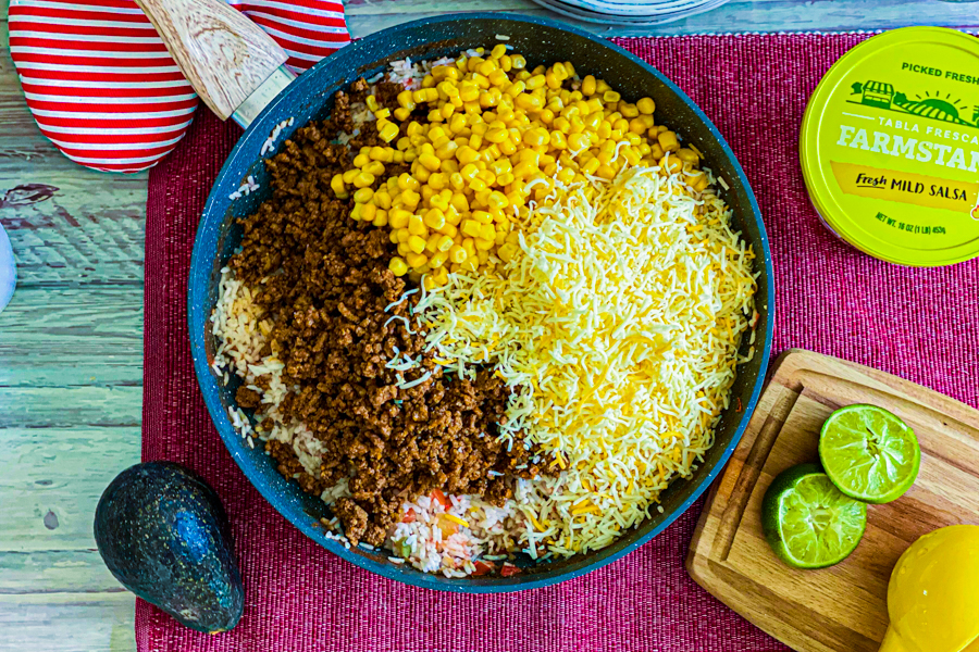 A pan piled high with cheese, corn, and ground beef before being stirred.