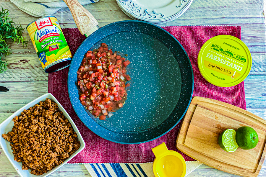 A skillet with water and salsa in it next to a bowl of ground beef, canned corn, and a sliced lime.
