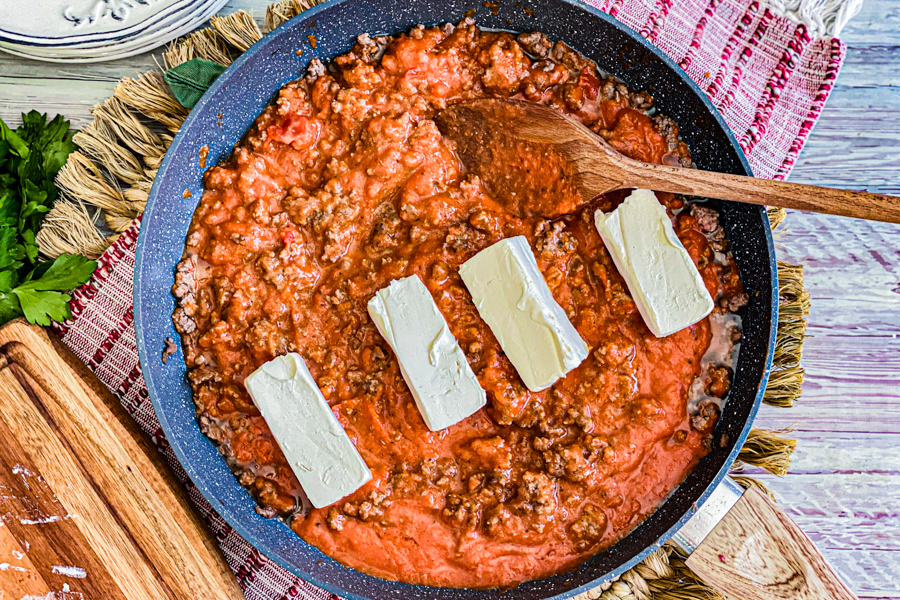 A skillet with ground beef, red sauce, and 4 slices of cream cheese on top that is about to be mixed in.