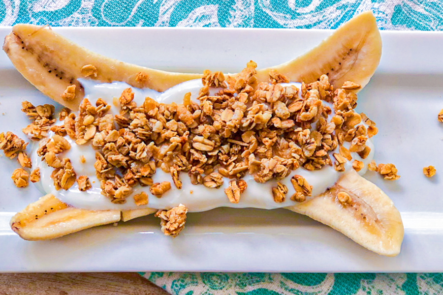A bana Split in half with yogurt and granola one top of it.