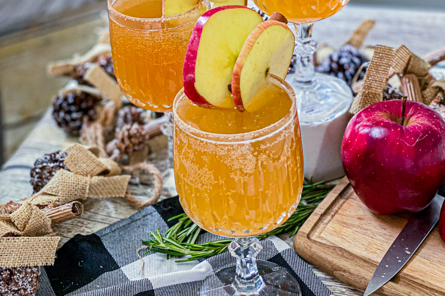 The final product of the Champagne Cider in a wine glass, garnished with an apple slice next to a small cutting board with a knife on it and a whole apple.