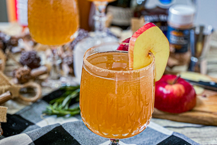 The final product of the Champagne Cider in a wine glass, garnished with an apple slice.