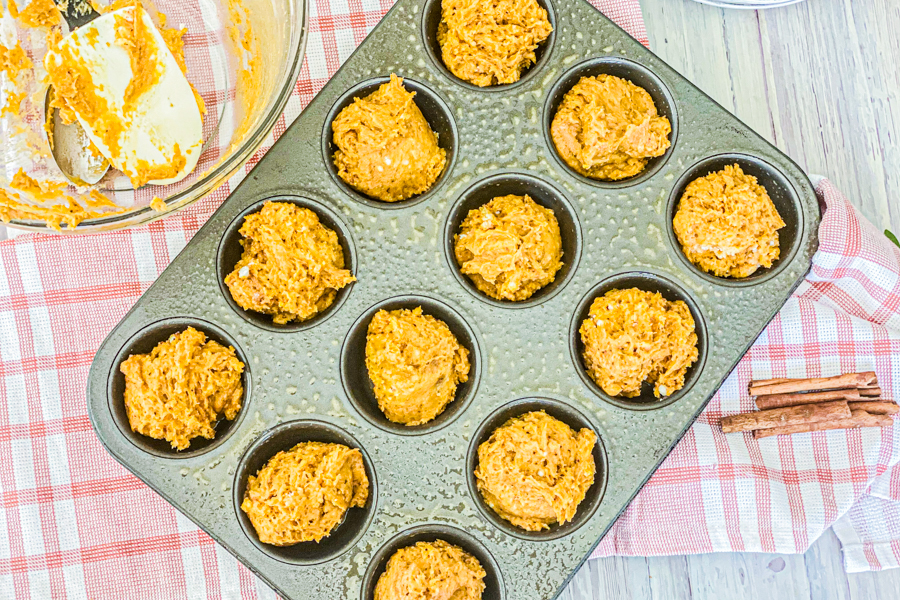 The pumpkin cake batter equally placed in a dark muffin tin.