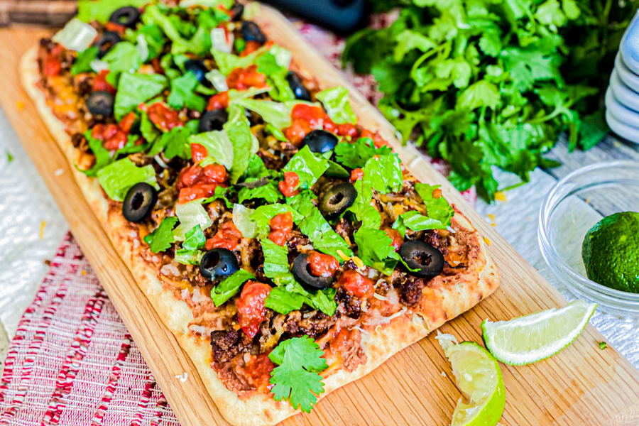 The Homemade Taco Pizza on a cutting board next to fresh cilantro, ready to be eaten.