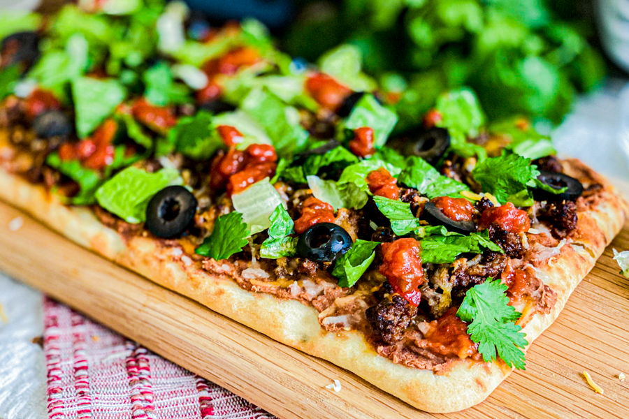 The Homemade Taco Pizza on a cutting board with all the ingredients on top.