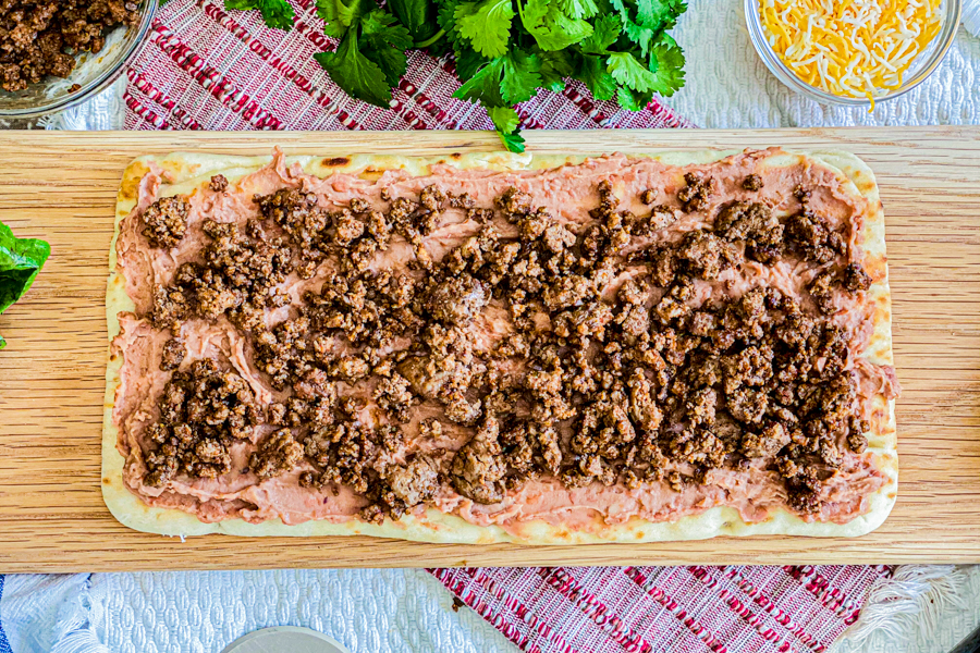 Naan flatbread laid out on a cutting board with a layer of refried beans and then taco meat.