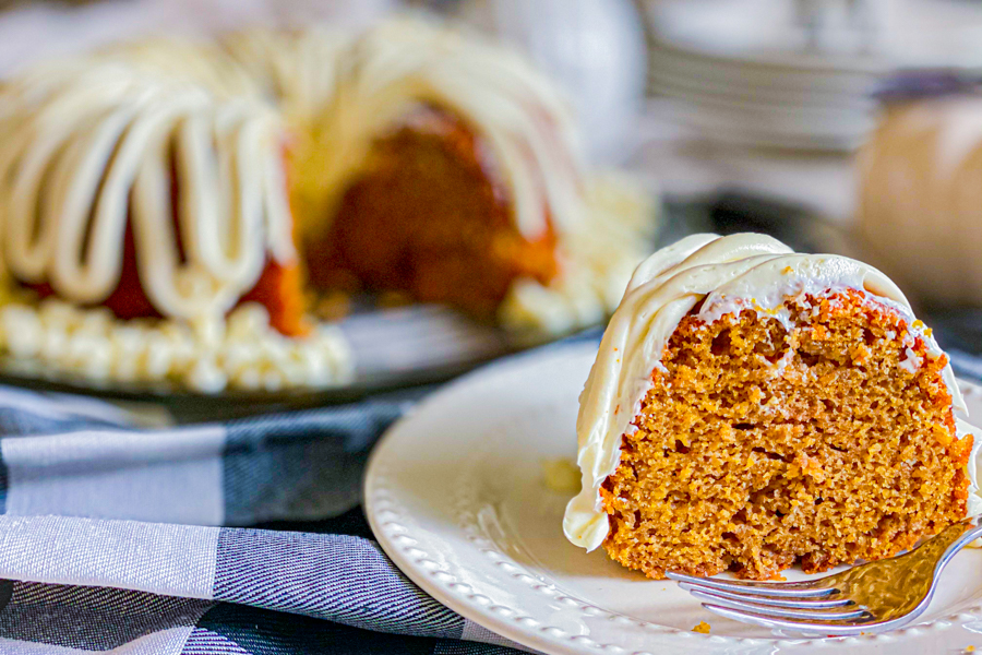 A slice of Pumpkin Spice Bundt Cake on a white plate with a form and the rest of the cake in the background.