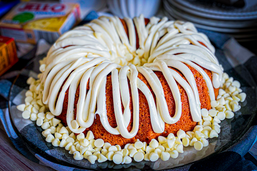 Pumpkin Spice Bundt Cake on a glass plate, garnished with cream cheese frosting and white chocolate chips.