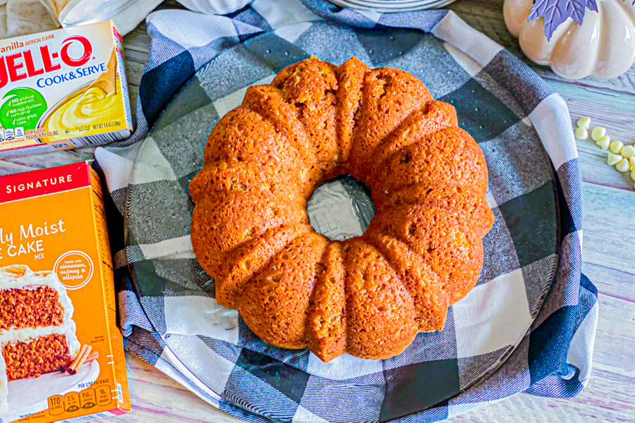 The Pumpkin Spice Bundt Cake, after being baked and flipped, sitting on a glass plate, while cooling.