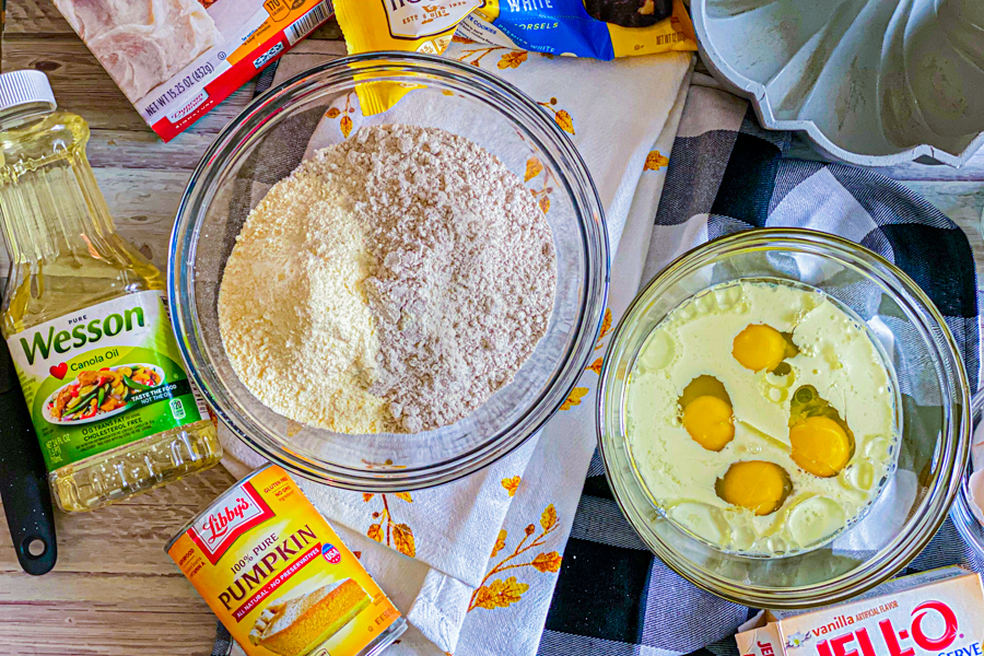 A glass mixing bowl with milk, eggs, and oil in it next to a glass bowl with the cake and pudding mix in it.