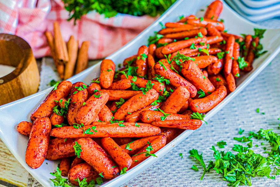 Roasted Maple Glazed Baby Carrots on a white serving dish ready to be eaten.