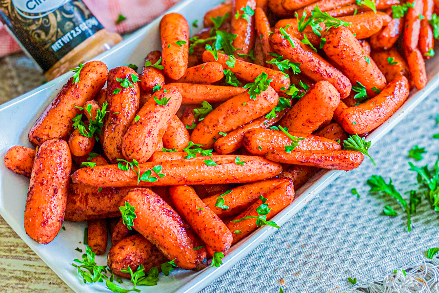 Roasted Maple Glazed Baby Carrots in a white dish, after being baked, garnished with fresh parsley.
