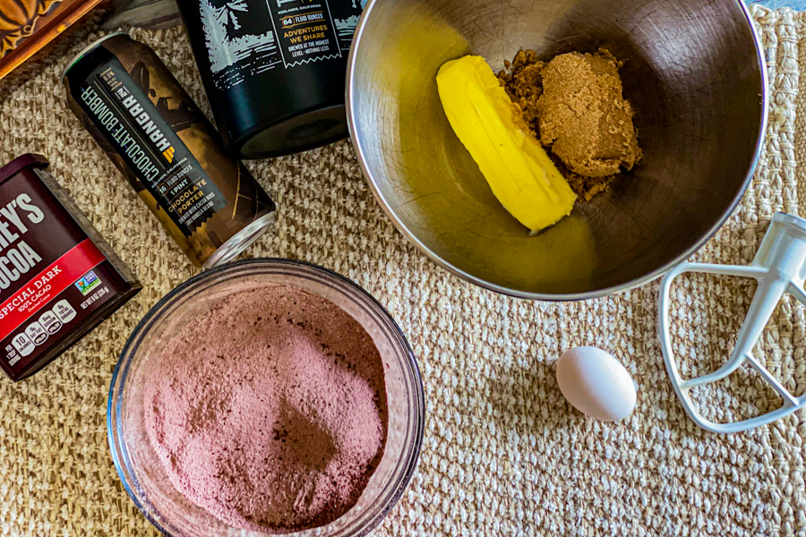 Flour and cocoa powder sifted in a clear bowl next to a mixing bowl with brown sugar and a stick of butter inside.