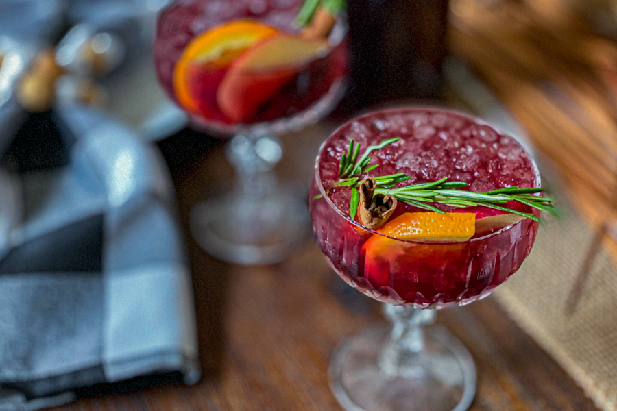 A glass of Sparkling Apple Cider Sangria Recipe garnished with a sprig of rosemary, a slice of orange and a cinnamon stick on a brown table, ready to serve.