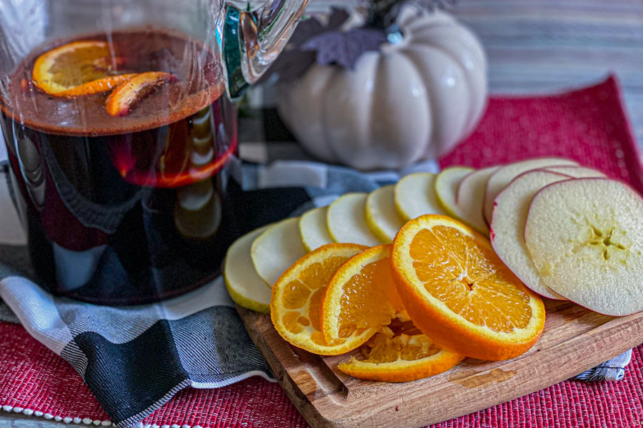 The pitcher with the sugar mixture and wine mixed together next to a cutting board of sliced apples, pears, and oranges.
