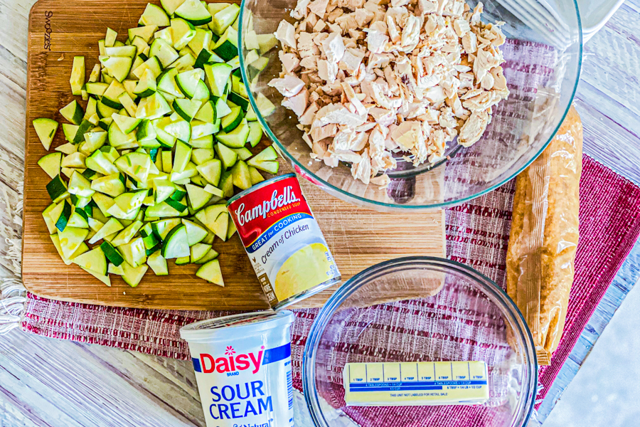 Diced zucchini on a cutting board next to a bowl with shredded chicken.