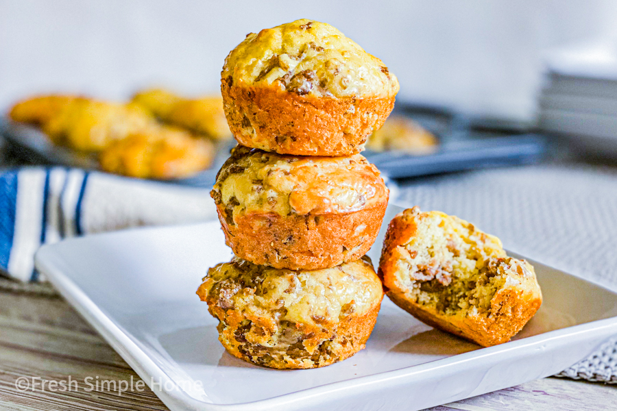 The Most Simple Pancake Sausage Bites on a white plate, stacked on top of each other, three muffins high.