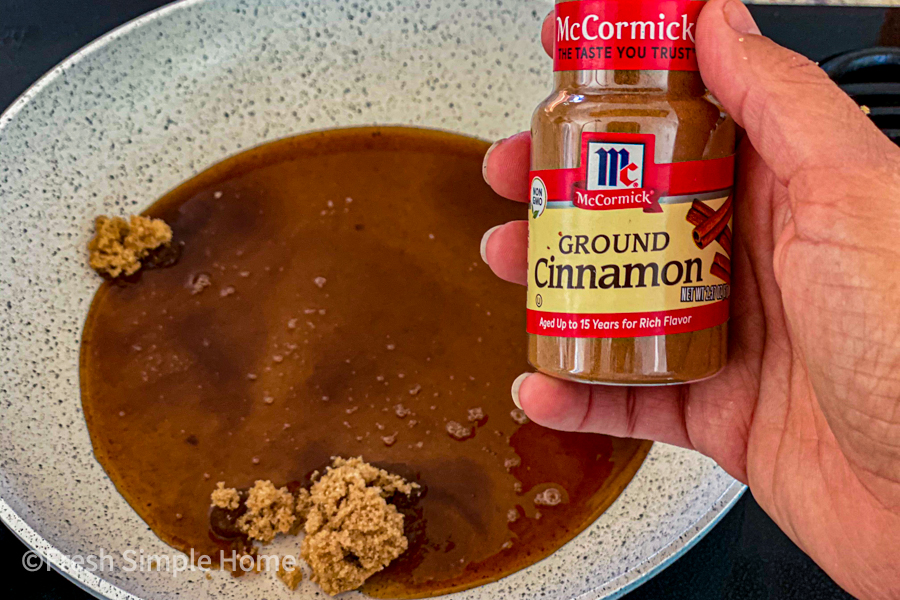 A sauce pan with water and brown sugar in it and someone holding up a bottle of cinnamon in front.