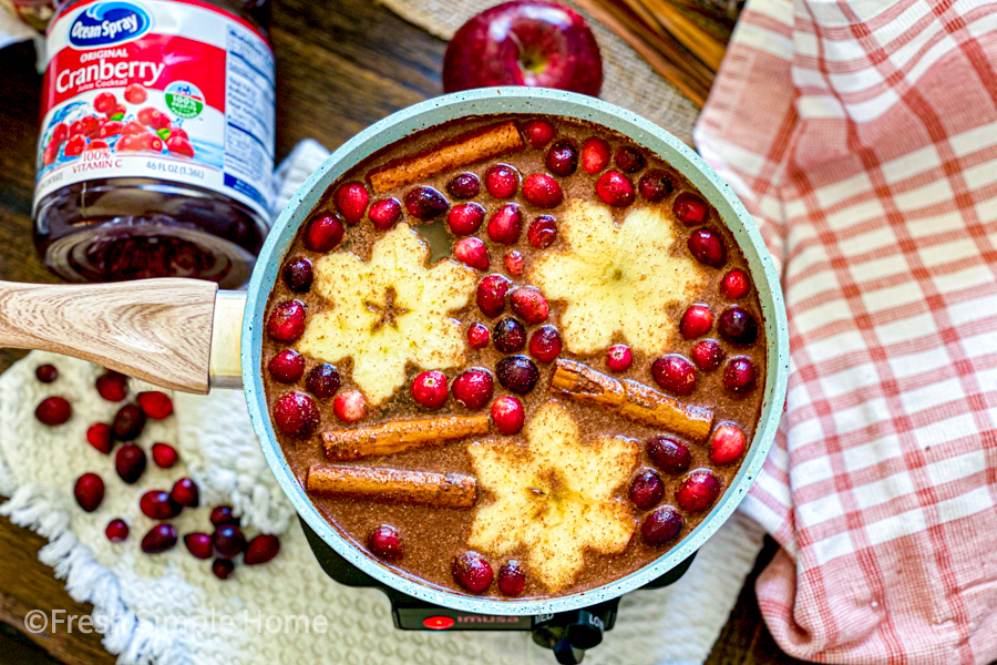 A large pot with all the ingredients in it, minus the bourbon, with fresh cranberries, cut apples, and cinnamon sticks floating on top.