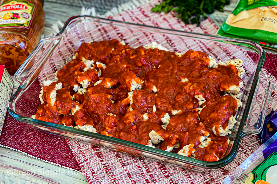 A glass baking dish with chicken and then marinara poured over top.