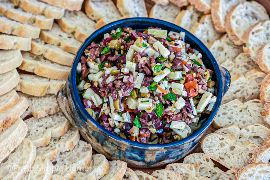 A bowl of my Chunky Green Olive Tapenade Recipe surrounded by cut baguette bread.