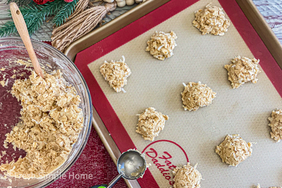 The dough for the Incredible Coconut Oatmeal Cookie Recipe being portioned on a cooking sheet.