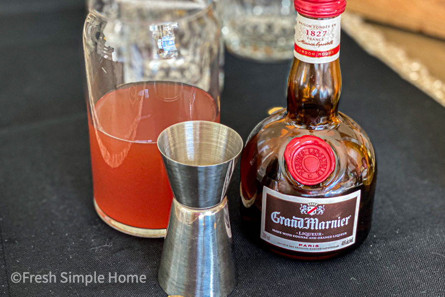 A glass with two ounces of cranberry juice and apple cider and 1.5 ounce of tequila and 1 ounce of Grand Marnier.